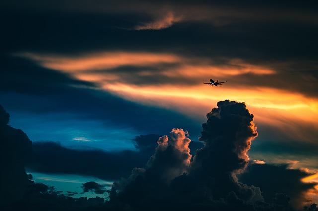Dopravné lietadlo vo vzduchu medzi oblakmi pred slnkom.jpg