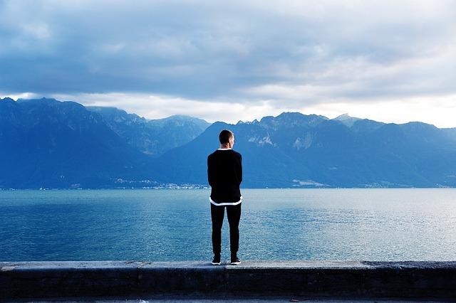 Muž stojaci na móle pri vode