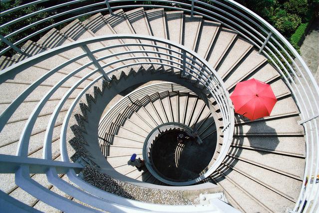 Dlhé zatočené schodisko, osoba s červeným dáždnikom, pohľad zhora