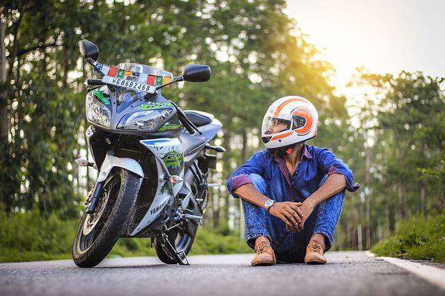 Muž sedí na ceste vedľa svojej motorky, moto-prilba
