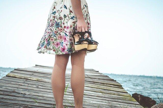 Žena v krátkych kvetovaných šatách a s punčochami na nohách stojí na móle a v ruke drží topánky.jpg