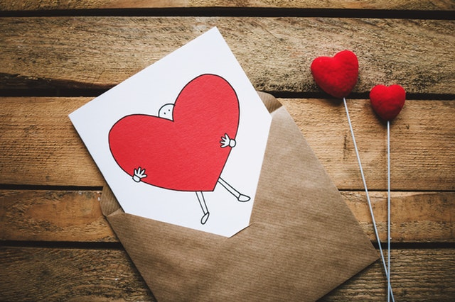 Hnedá obálka s kartou, na ktorej je panáčik držiaci srdce.jpg