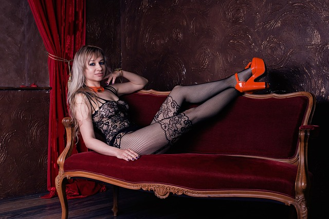 Žena v erotickej bielizni a vysokých podpätkoch sedí na gauči.jpg