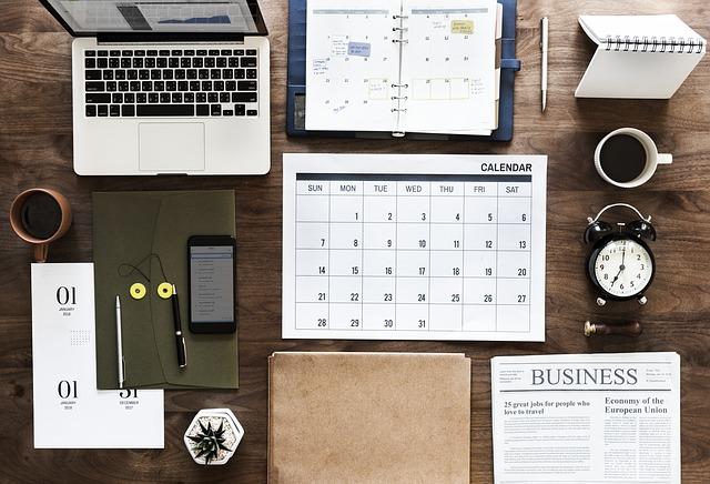 Drevený stôl, kancelárske potreby, počítač a kalendár.jpg